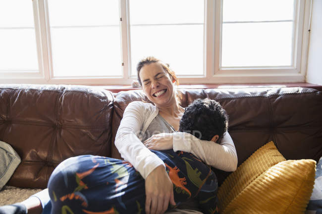 Happy, carefree mother cuddling with son on living room sofa — Stock Photo