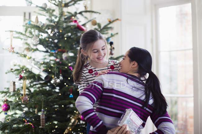 Madre giocosa che nasconde il regalo di Natale alla figlia in soggiorno — Foto stock