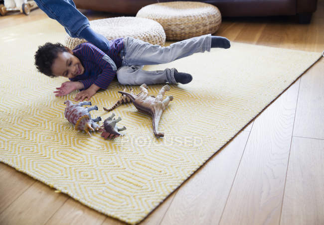 Playful boy with dinosaur toys on living room floor — Stock Photo