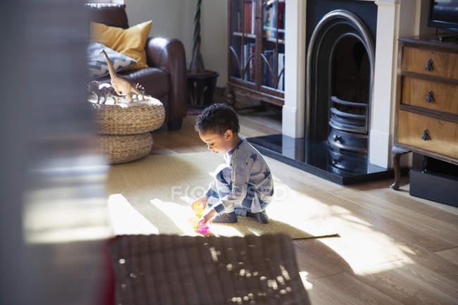 Junge im Pyjama spielt mit Spielzeug auf Wohnzimmerboden — Stockfoto