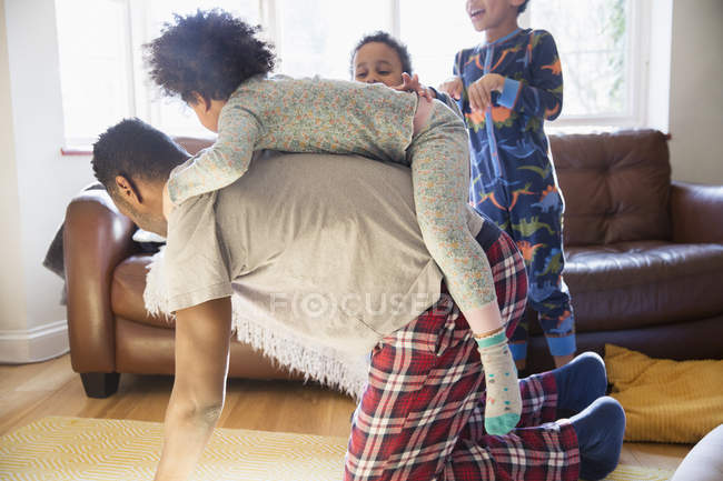 Playful father in pajamas carrying daughter on back — Stock Photo