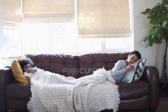 Frère et sœur se relaxent, regardant la télévision sur le canapé du salon — Photo de stock