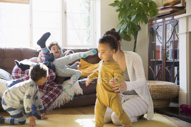 Jovem família de pijama brincando na sala de estar — Fotografia de Stock