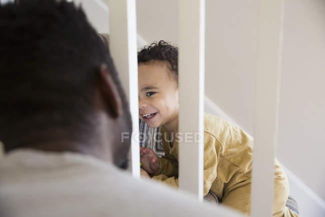 Verspielter kleiner Junge steigt Treppe hinauf, lächelt Vater an — Stockfoto