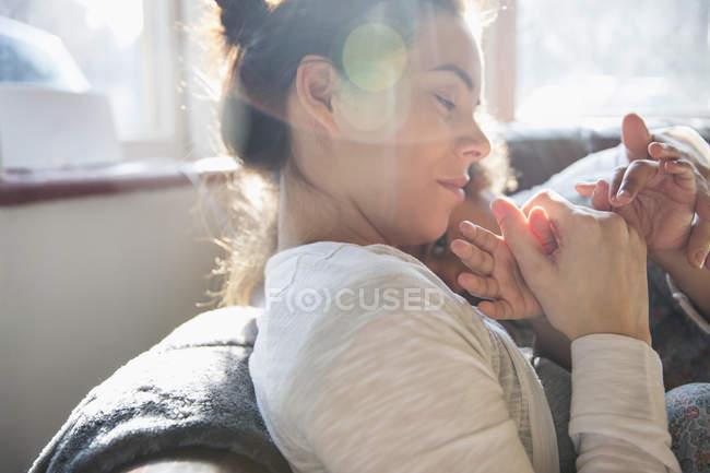 Ласковые, нежные мать и дочь держатся за руки — стоковое фото