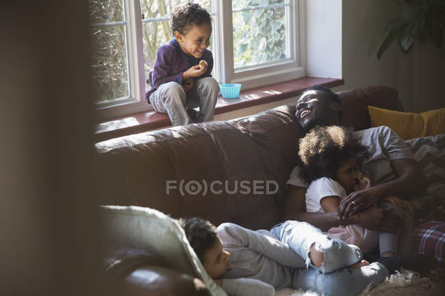 Pai feliz e crianças abraçando no sofá da sala de estar — Fotografia de Stock