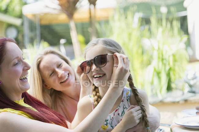 Lesbian couple and daughter playing with sunglasses on patio — Stock Photo