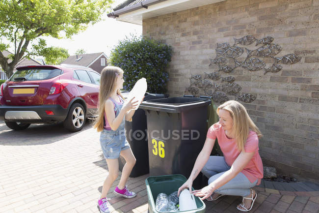 Mother and daughter recycling plastic outside house — Stock Photo