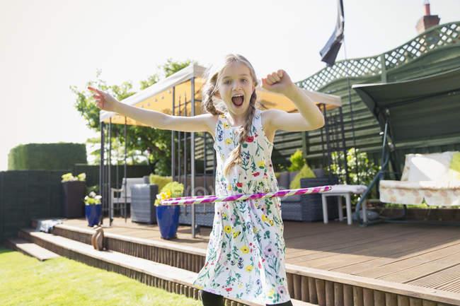 Портрет грайливий дівчинка, граючи з пластикових Хооп Сонячний задньому дворі — стокове фото