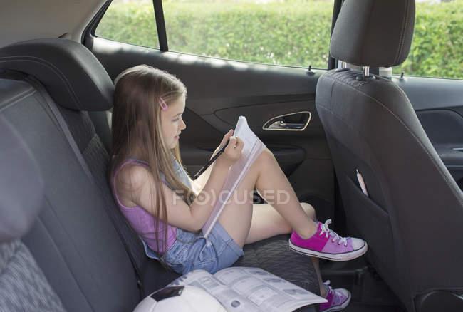 Дівчина робити домашнє завдання в задньому сидінні автомобіля — стокове фото