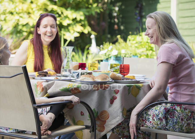 Lesbian couple and daughter enjoying lunch on patio — Stock Photo