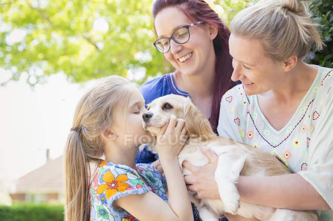 Ласкава лесбійську пару і дочка цілуватися собака — стокове фото