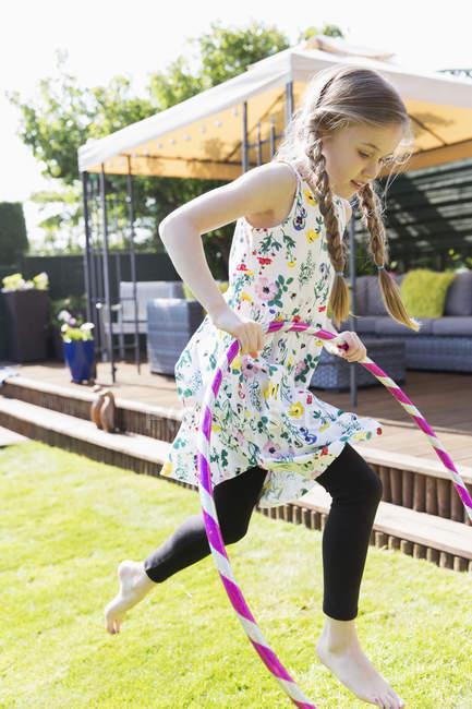 Дівчинка, граючи з пластикових Хооп у Сонячний дворі — стокове фото