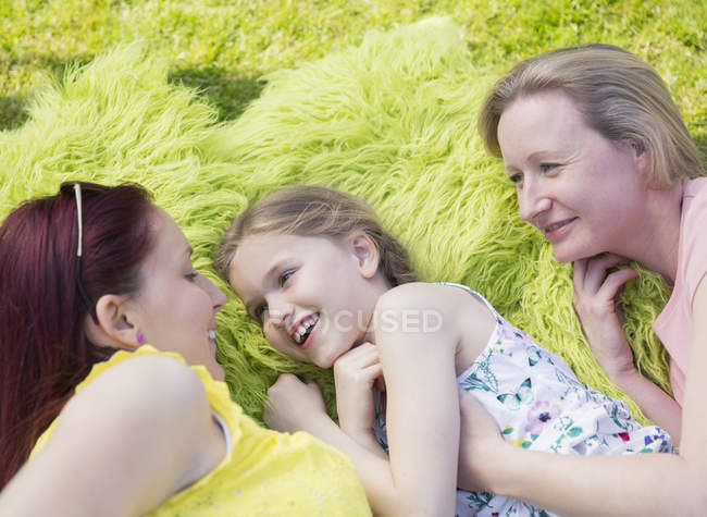 Affectionate lesbian couple and daughter laying in grass — Stock Photo