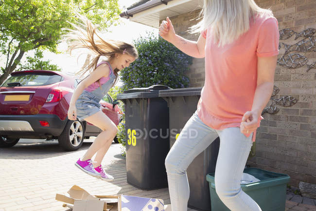 Mother and playful daughter breaking down cardboard for recycling outside house — Stock Photo