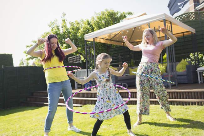 Пару лесбіянок і дочка, граючи з пластикових обручі в Сонячний дворі — стокове фото