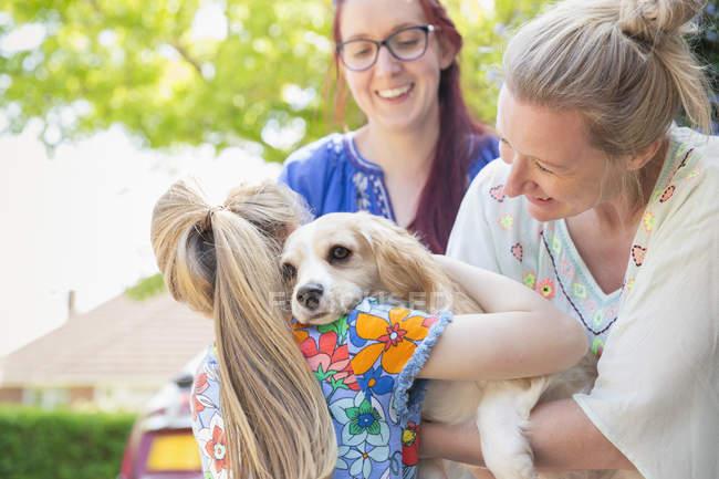 Lesbisches Paar und Tochter umarmen niedlichen Hund — Stockfoto