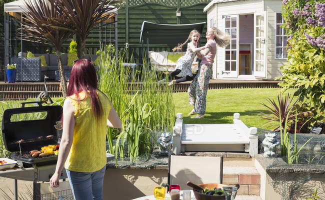 Lesbian couple and daughter playing and barbecuing in sunny backyard — Stock Photo