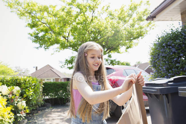 Girl recycling in sunny driveway — Stock Photo