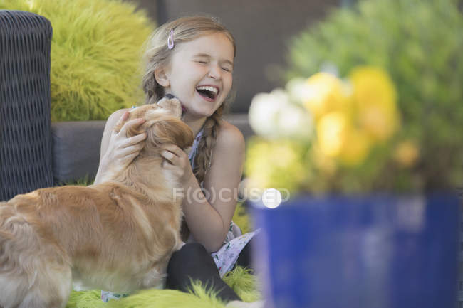 Dog kissing laughing girl on patio — стокове фото