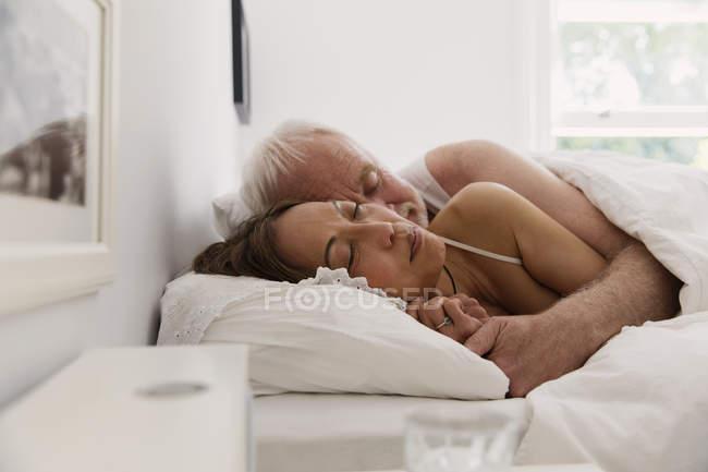 Безтурботний старший пара спати в ліжку — стокове фото