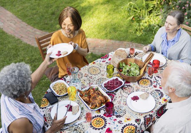 Amigos seniores desfrutando de almoço na mesa do pátio — Fotografia de Stock