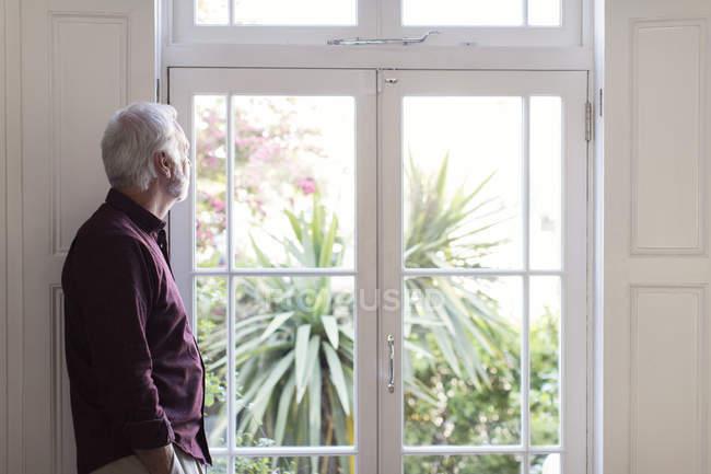 Sênior atencioso olhando pela janela — Fotografia de Stock