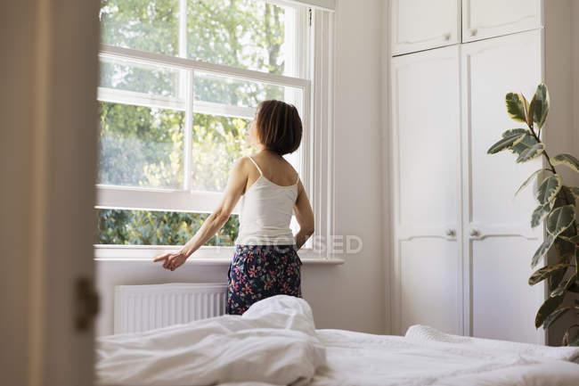 Nachdenklich senior Frau Schlafzimmerfenster schauen — Stockfoto