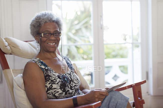Porträt lächelnde, selbstbewusste Seniorin mit digitalem Tablet — Stockfoto