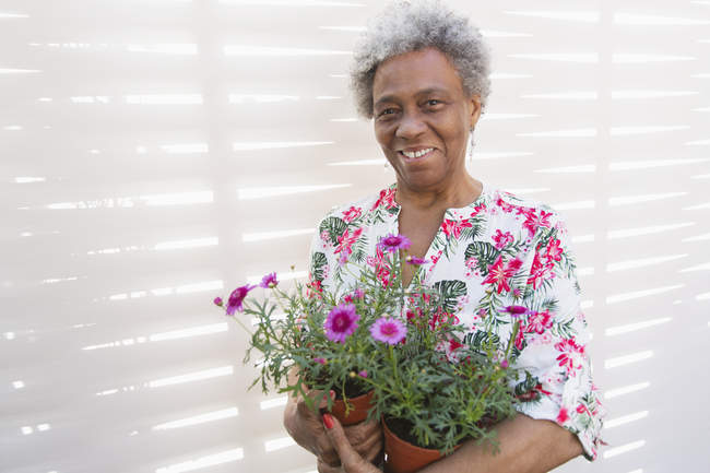Portrait smiling, confident active senior woman gardening, holding flowerpots — Stock Photo