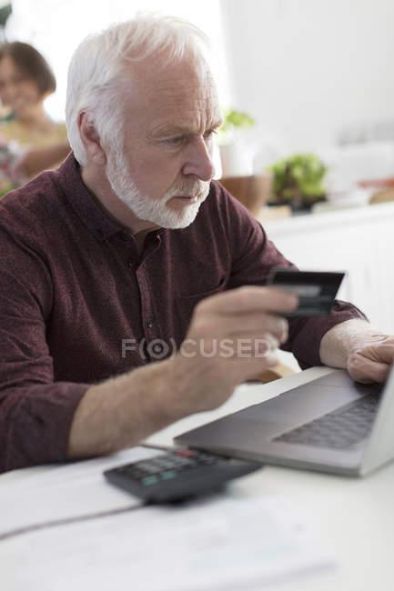 Focused senior man with credit card paying bills at laptop — Stock Photo