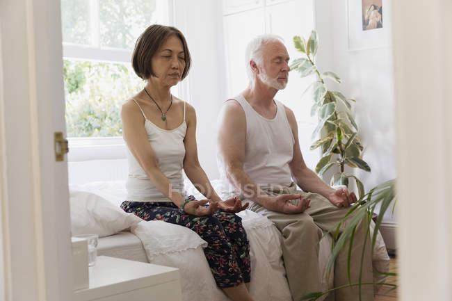 Pareja senior sereno meditar en la cama - foto de stock