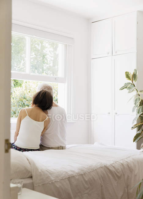 Serene senior couple sitting on bed and looking out window — Stock Photo