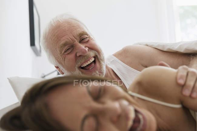 Pareja senior juguetona, cariñosa en la cama - foto de stock