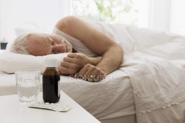 Hombre mayor cansado durmiendo al lado de la mesa de noche con jarabe para la tos y medicina - foto de stock