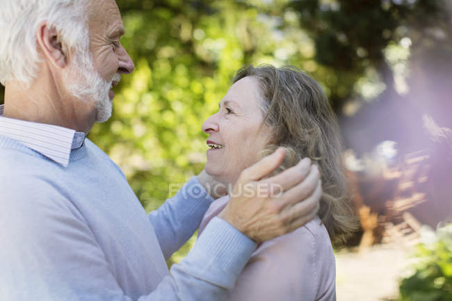 Affectionate senior couple hugging in garden — Stock Photo