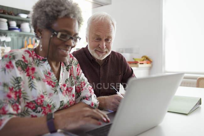 Senior couple paying bills at laptop in kitchen — Stock Photo