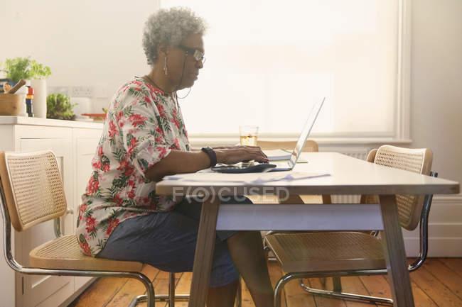 Senior woman paying bills at laptop in kitchen — Stock Photo