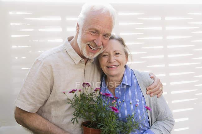 Porträt glückliches rühriges Seniorenpaar mit Blumentöpfen — Stockfoto