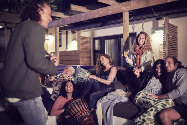 Happy friends hanging out, playing music on patio at night — Stock Photo