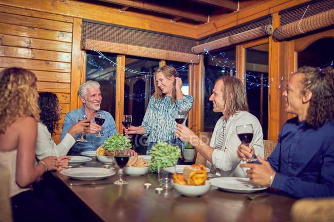 Amigos comemorando, bebendo vinho tinto e desfrutar de um jantar no camarote — Fotografia de Stock