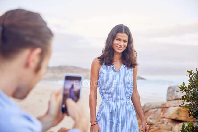 Giovane con smart phone fotografare fidanzata in spiaggia — Foto stock