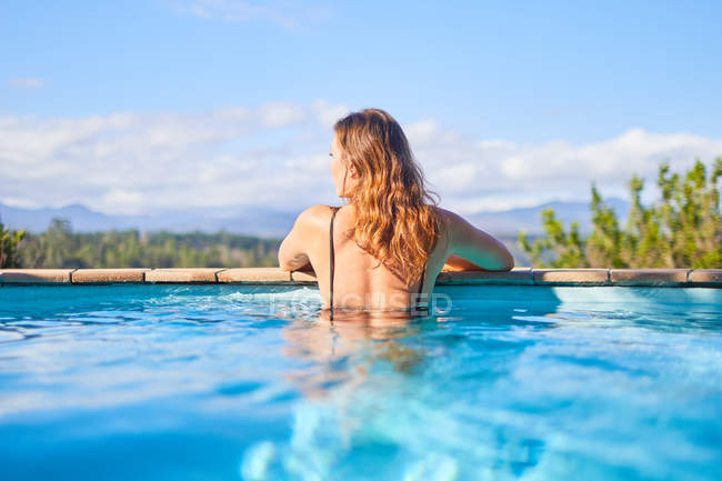 Serene woman in sunny swimming pool — Stock Photo