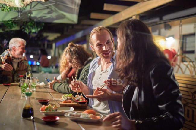 Пара еды, наслаждаясь суши на патио в ночное время — стоковое фото