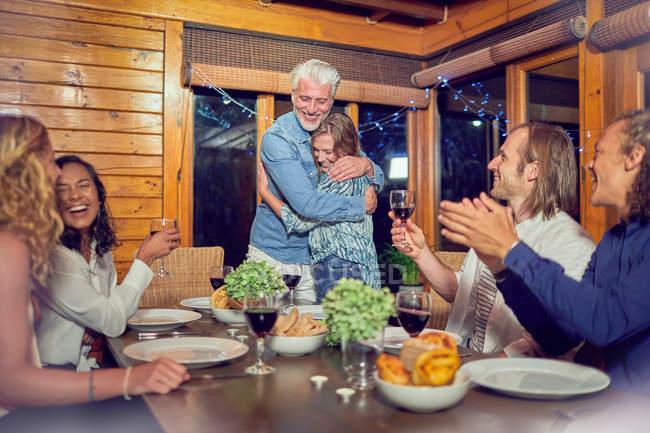 Amigos aplaudiendo a pareja cariñosa abrazándose en la mesa - foto de stock