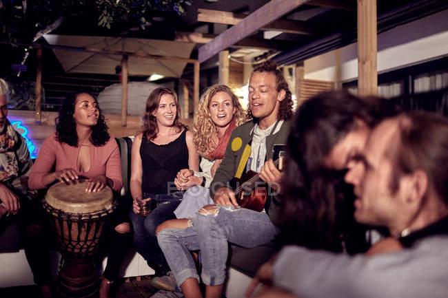 Друзі гуляти, відтворення музики на внутрішній дворик вночі — стокове фото