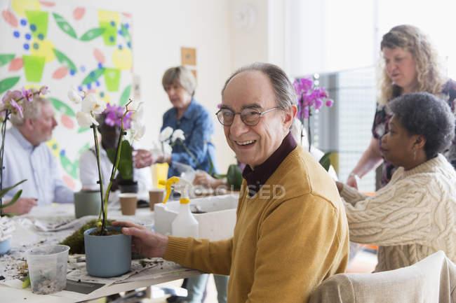 Портрет, посміхаючись, впевнено активних старшим людина, насолоджуючись квітка організацію класу — Stock Photo
