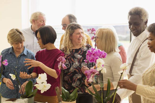 Активные пожилые люди наслаждаются классом аранжировки цветов — стоковое фото