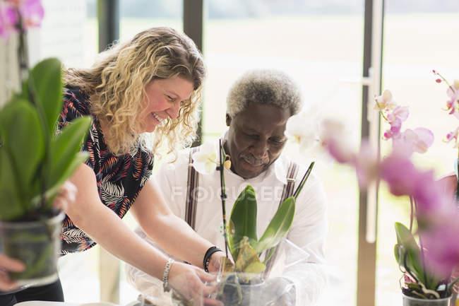 Instructeur féminin aidant l'homme âgé actif dans la classe d'arrangement de fleurs — Photo de stock