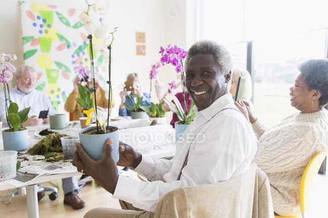 Portrait homme âgé actif confiant appréciant la classe d'arrangement de fleurs — Photo de stock